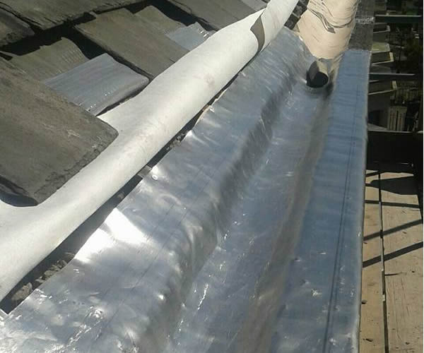roofing work - stone guttering repairs during